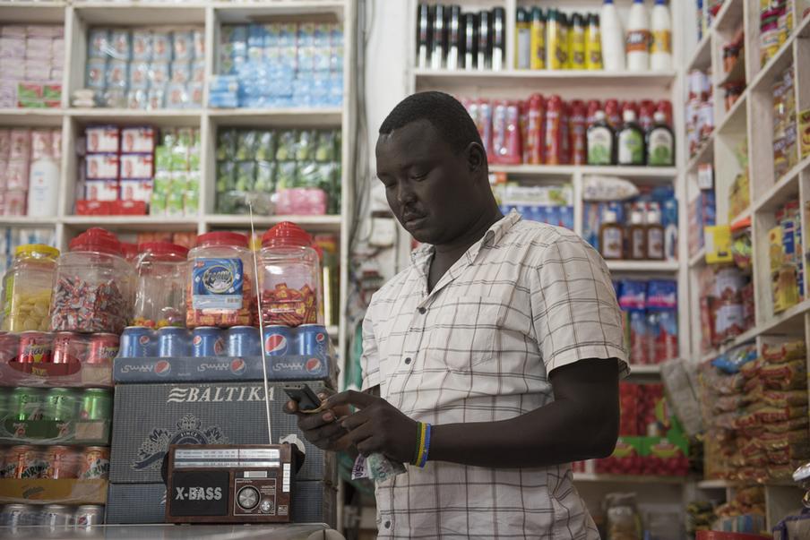 Gore Jopseph luistert graag naar de radio tijdens werktijd om op de hoogte te blijven van het nieuws. Juba, Zuid-Soedan. Foto: Charles Lomodong (voor De Correspondent)