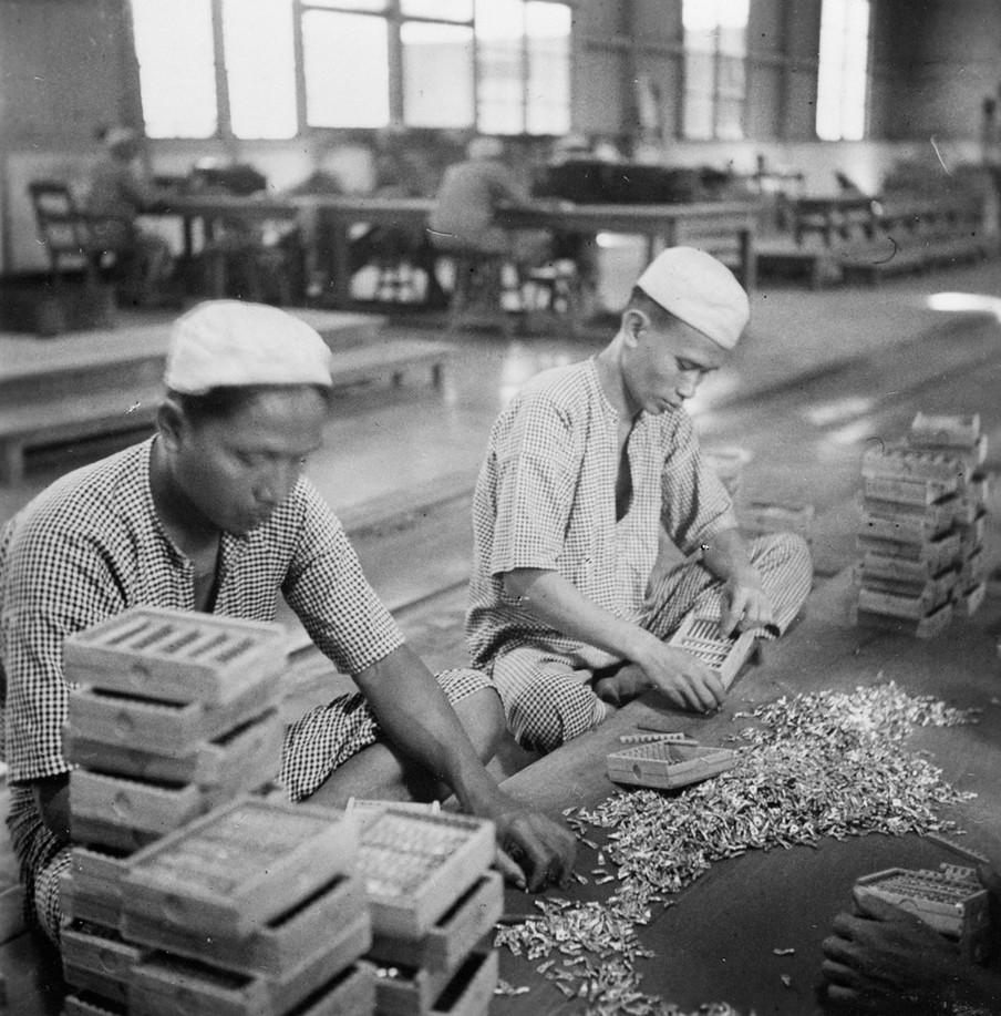 In de opiumfabriek te Batavia worden de tubes in houten doosje verpakt, Java, 1936. Foto: Foto: Collectie Nationaal Museum van Wereldculturen. Coll.nr. TM-10012174