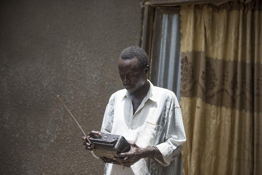 In opdracht van De Correspondent zocht Charles Lomodong Zuid-Soedanese radioluisteraars op. Dit is Thomas Ali, terwijl hij via de radio een nieuwsuitzending volgt. Juba, Zuid-Soedan.