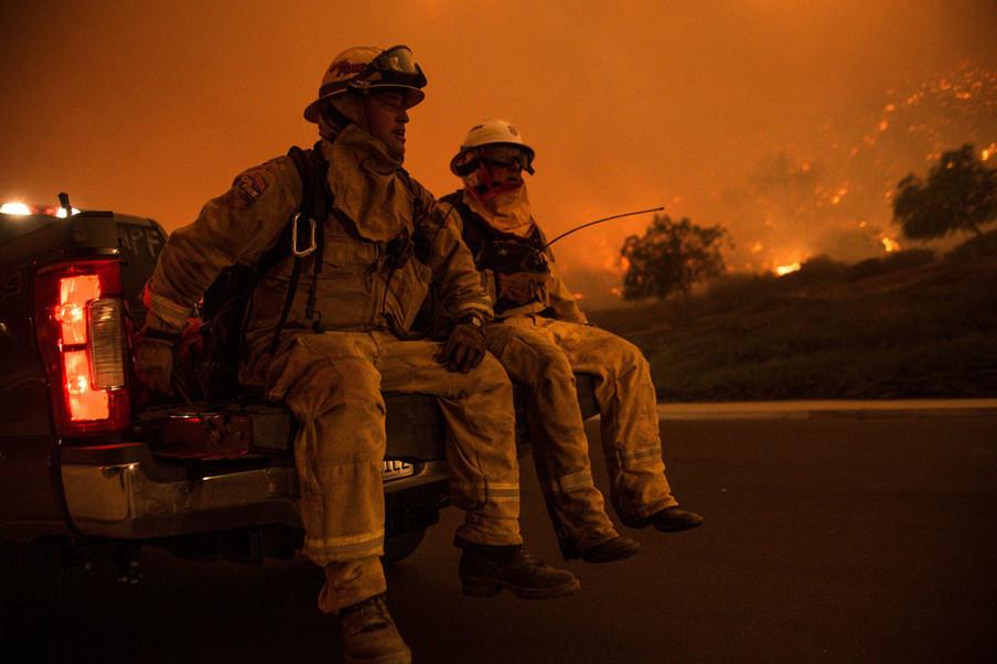 Twee brandweermannen nemen een pauze na uren tegen vuur gevochten te hebben in Cleveland National Forest, 9 augustus 2018. Foto: Chris Rusanowsky / HH