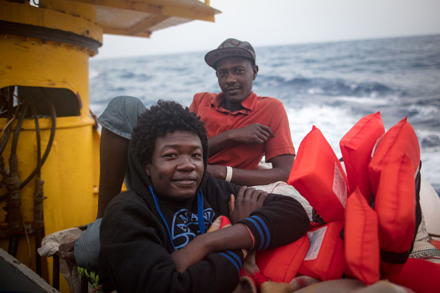 Twee migranten poseren op het dek van de Sea-Watch 3. De voorste man is doofstom, maar organiseert toch dagelijks het uitdelen van het voedsel. 8 juni 2018. Foto: Erik Marquardt