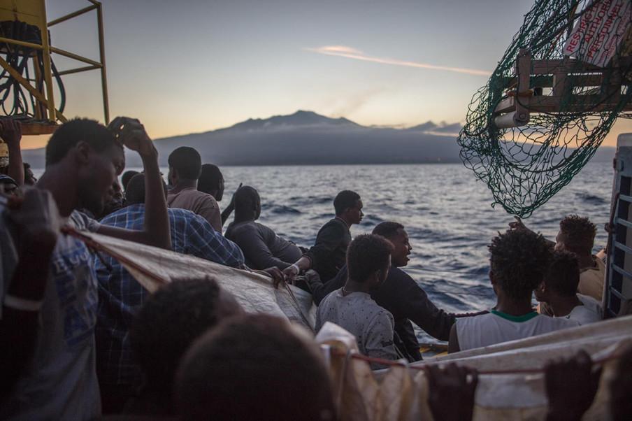Mensen aan boord van de overvolle Sea-Watch 3 zijn blij om de kust van Sicilië te zien. Op bevel van de Italiaanse autoriteiten zullen ze daar aanmeren, 8 juni 2018. Foto: Erik Marquardt