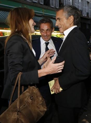 Bruni en Sarkozy begroeten Bernard-Henri Lévy voor aanvang van zijn voorstelling. Foto: ANP