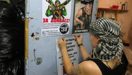 Een vrouw hangt in een Moskouse verblijfplaats van de nationaal-bolsjewieken een oproep op om op 31 januari te gaan protesteren ter ondersteuning van de pro-Russische rebellen in de Oost-Oekraïense regio Donbass.