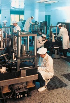 Foto boven: ASML's eerste kantoor (het 'houten noodgebouwtje'). Foto midden: ASML's eerste chipmachine, de PAS2000. Foto onder: Assemblage van machines in de 'cleanroom'. Foto's: ASML.
