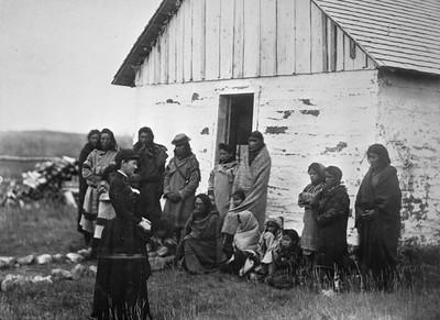 Groep ouders en kinderen voor een leerlingenverblijf, datum en plaats onbekend. Foto: Library and Archives Canada