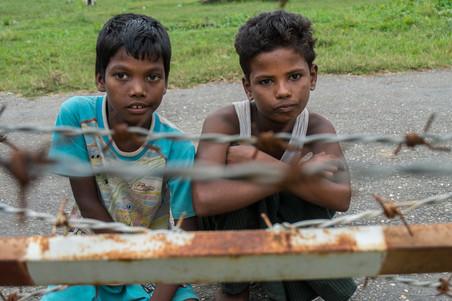 Twee kinderen aan de andere kant van de weg. Ze mogen niet verder dan het hek. Foto: Andreas Stahl