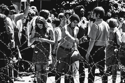Demonstrators place flowers on a barbed wire fence in People's Park on the campus of the University of Berkeley, 1969. Photo by David Fenton/Getty Images