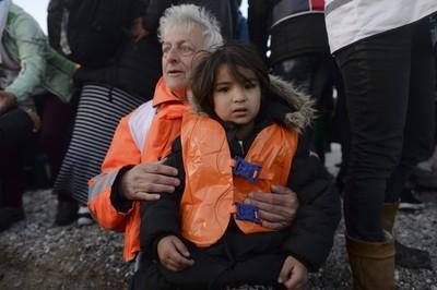 Een vrijwilliger met een jonge vluchteling die net gearriveerd is op Lesbos. Foto: Hollandse Hoogte