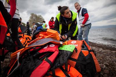Een vrijwilliger verzameld reddingsvesten aan de kust van Skala Skamnias. Foto: Hollandse Hoogte