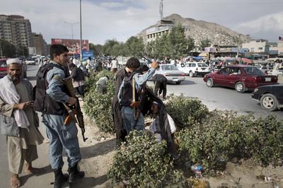 Leden van de Afghaanse Nationale Politie jagen drugsgebruikers weg van een drukke straat in centraal Kabul.
