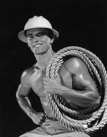 Studio portrait of a bare-chested construction worker with glistening muscles, wearing a hard hat and holding thick rope coiled over one shoulder. Photo by Lambert / Getty Images