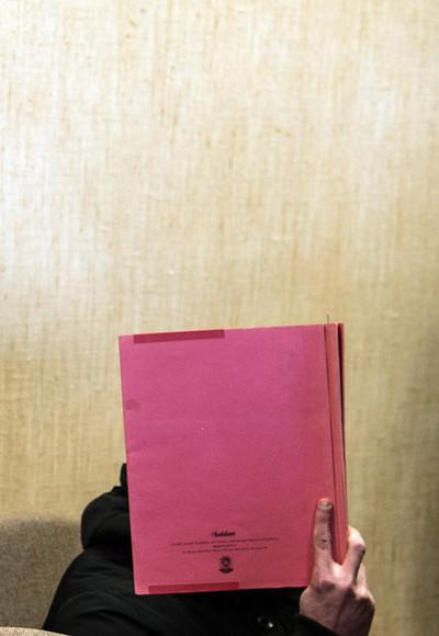 Een verdachte houdt een dossiermap voor zijn hoofd tijdens de rechtszaak op 24 februari, 2016. Drie mannen worden beschuldigd van diefstal tijdens oudejaarsnacht in Keulen. Foto: Federico Gambarini / DPA
