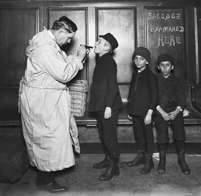 Kinderen worden gecheckt door een dokter na aankomst op Ellis Island. New York, 1911. Foto: Getty