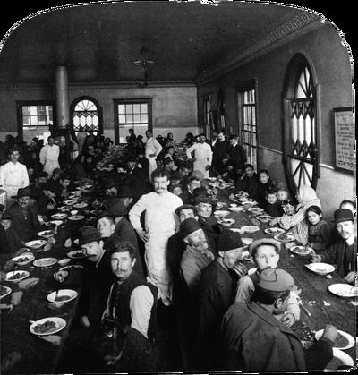 Immigranten zitten aan tafel in de eetzaal van Ellis Island, de mannen in het wit zijn ober in de eetgelegenheid. Foto: Getty
