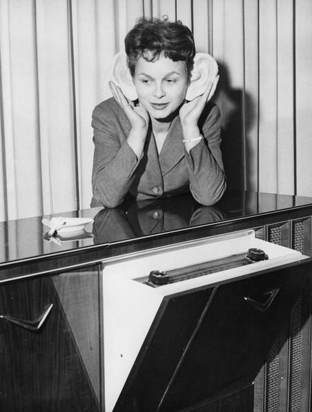 Een vrouw luistert naar muziek op een beurs in Duitsland, 1958. Foto: Keystone / Getty Images