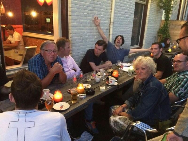 Aan een grote eettafel op het terras van een café in de Utrechtse wijk Lombok.