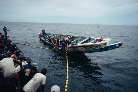 Vissers staan klaar om visnetten binnen te halen. Ze zingen en klappen. Foto: Liu Yuyang / Greenpeace