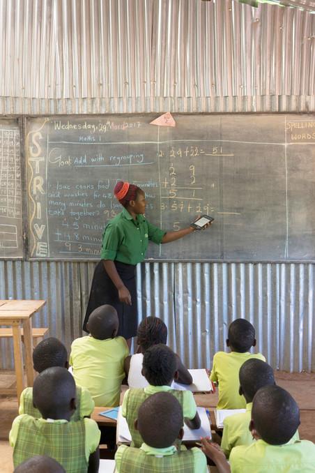 Een docent met een bridgetablet, de Nook, op een basisschool van Bridge International Academies in Mpigi, Oeganda. Foto: Jon Rosenthal / Alamy