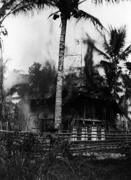 Een huis is in de brand gezet in een dorp op Sulawesi, 18 december 1946. Militair Kavelaars is erbij en neemt een foto van de brand. Hij maakte geen deel uit van de bataljons van Vermeulen, Stufkens en Rijborz.