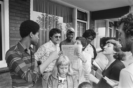 Bewoners Coenhotelflat (Amsterdam) protesteren tegen de slechte huisvesting van Surinamers. Krantenkop: 'Coenhotel: ghetto voor Surinamers'. Foto: Rob Bogaerts / Nationaal Archief