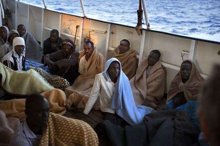 Mannen zitten aan boord van de Golfo Azzurro nadat zij gered zijn ten noorden van Zuwarah op 21 juni 2017. Foto: Emilio Morenatti / AP