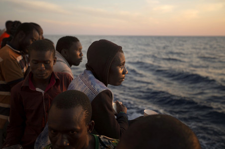 Migranten zijn aan boord van de Golfo Azzurro terwijl dit reddingsschip de haven van Pozallo binnenvaart. Er zijn honderden migranten aan boord die zijn gered door leden van Proactiva Open Arms op 17 juni, 2017. Foto: Emilio Morenatti / AP
