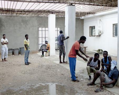 Migranten in het openluchtgedeelte van het Al-Khoms-detentiecentrum, november 2015. Foto: Magnum Photos / HH