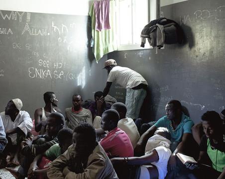 Migranten zitten in een overvolle ruimte van het Garabulli-detentiecentrum in Tripoli, november 2015. Foto: Magnum Photos / HH
