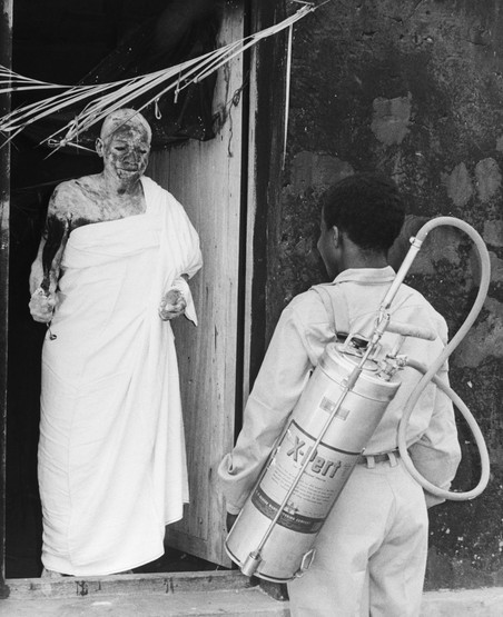 De sjamaan Togbe Hayi Kwamla uit Adaklu Abuadi praat met een DDT-sprayer in 1965, Ghana. Foto: Bettmann / Getty Images