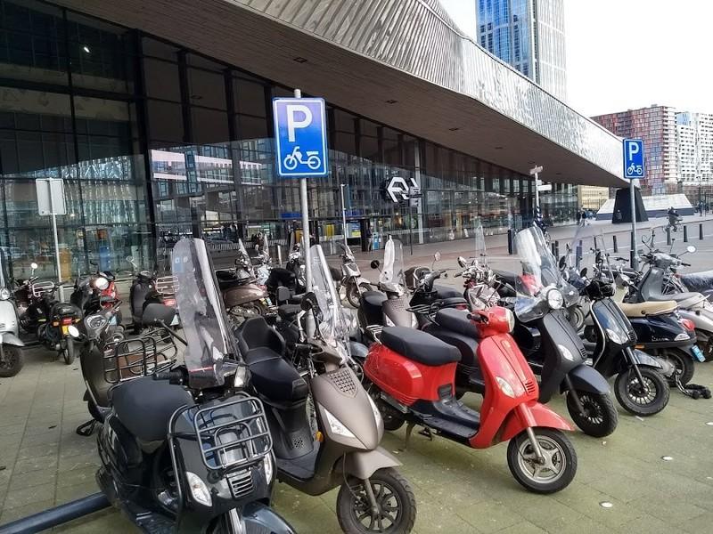 Scooteraars mogen gratis parkeren op 25 stappen van de ingang van Rotterdam Centraal, aan het fietspad en het fietstunneltje. Fietsers niet. Foto Thalia Verkade