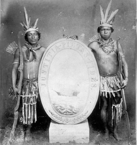 Twee Carib-mannen tonen het wapenschild van Suriname en vormen daarbij het wapen van Suriname, 1887. Foto: J.E. Muller / Tropenmuseum