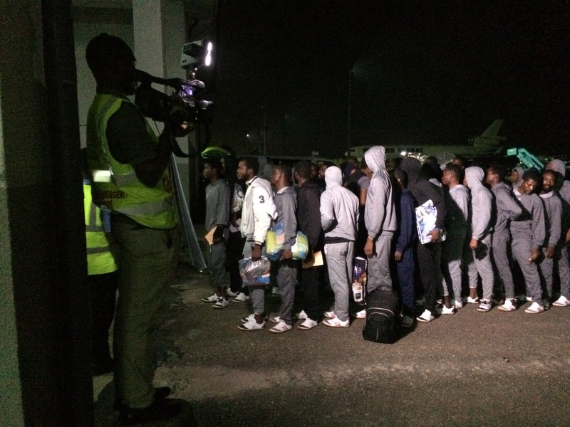 De migranten wachten in de rij om geregistreerd te worden.