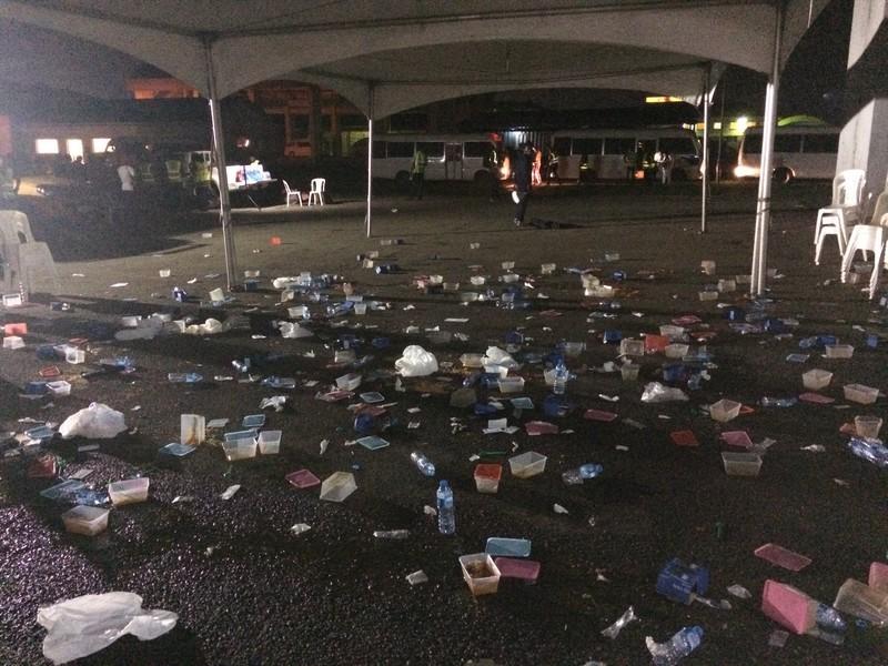 Als de migranten in bussen zijn afgevoerd, blijft alleen een berg afval achter op het vliegveld.