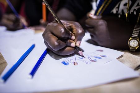 Terugkeerders tekenen tijdens een IOM-training voor bedrijfsvaardigheden in Lagos, Nigeria, op 16 oktober 2018. Foto: Tom Saater (voor De Correspondent)