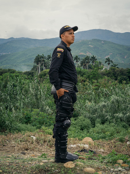 Een agent kijkt vanaf een afstandje toe terwijl duizenden Venezolanen de Simón Bolívar-brug oversteken om Colombia te bereiken, 2018. Foto: Greg Kahn