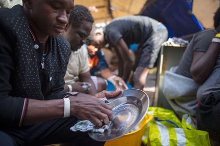Boven: Aan boord van de Sea-Watch 3 bekijken migranten een zelfgemaakte kaart om beter te begrijpen waar ze zijn, 6 juni 2018. Onder: Migranten helpen met de afwas na de lunch, 8 juni 2018. Foto's: Erik Marquardt