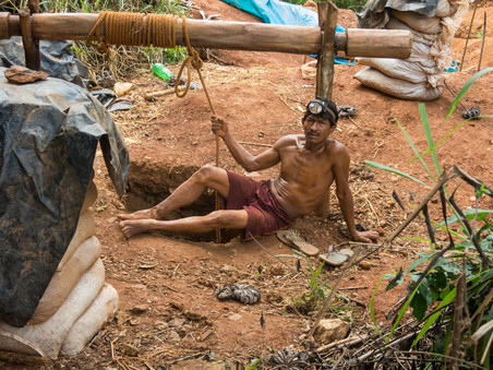 Een mijnwerker poseert voor de foto nadat hij uit een smalle geïmproviseerde tunnel is gekropen bij El Callao.